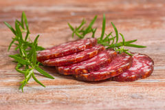 Salami slices with pepper and rosemary Royalty Free Stock Photography