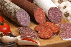 Salami and slices salami on a timber board. Salami and some slices salami on a timber board Stock Images
