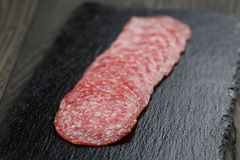 Salami slices slate board Royalty Free Stock Image