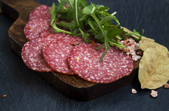 Salami slices with spices and arugula Stock Photo