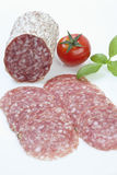 Salami slices and tomato on white background Stock Images