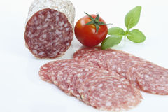 Salami slices and tomato on white background Stock Image