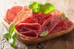 Salami slices in wooden plate Stock Images