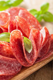 Salami slices in wooden plate Royalty Free Stock Photo