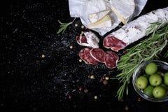 Salami, smoked sausage, olives, rosemary. Spanish fuet snack. Salami, smoked sausage, olives and rosemary. Traditional spanish fuet snack. Above view, white royalty free stock photos