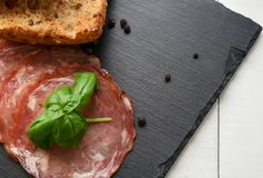 Salami smoked sausage slices basil leaves and peppercorns on black stone background stock image