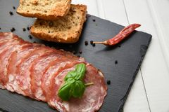 Salami smoked sausage slices basil leaves and peppercorns on black stone background royalty free stock images