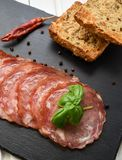 Salami smoked sausage slices basil leaves and peppercorns on black stone background royalty free stock photography