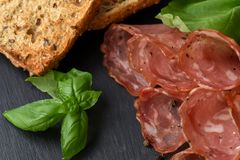 Salami smoked sausage slices basil leaves and peppercorns on black stone background stock photos