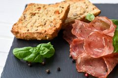 Salami smoked sausage slices basil leaves and peppercorns on black stone background royalty free stock photos