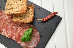 Salami smoked sausage slices basil leaves and peppercorns on black stone background royalty free stock image