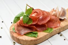 Salami smoked sausage slices basil leaves and peppercorns on white background stock images