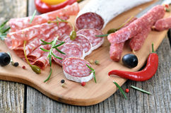 Salami snack. Snack with delicious French and Italian salami on a wooden cutting board Royalty Free Stock Photo