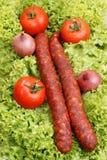 Salami on some fresh organic salad. Home made salami on some fresh organic salad Stock Images