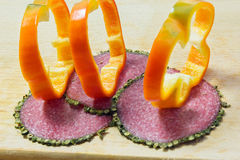 Salami with spices on the edges and bell pepper rings Royalty Free Stock Photo