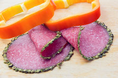 Salami with spices on the edges and bell pepper rings Royalty Free Stock Images