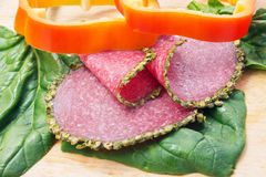 Salami with spices on the edges, spinach, bell pepper rings Stock Image