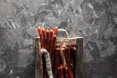 Salami with spices in an old tray. On a dark gray background stock images