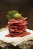 Salami stack. Sliced salami stack with olive on top Royalty Free Stock Photo