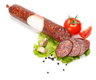 Salami stick with blank label and slices around Royalty Free Stock Images