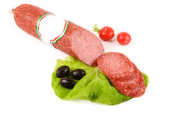 Salami stick with blank label and slices around Stock Photo