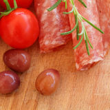 Salami, tomatoes, rosemary and olives Royalty Free Stock Photography