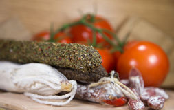 Salami with tomatoes on wood. French salami close-up on wooden table royalty free stock photo