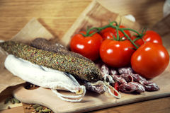 Salami with tomatoes on wood. French salami on wooden table royalty free stock images