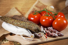 Salami with tomatoes. On wooden table royalty free stock photo