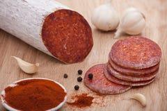 Salami tradicional de la paprika a bordo con ajo Foto de archivo libre de regalías