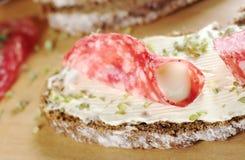Salami-und Frischkäse auf Brown-Brot stockfotografie