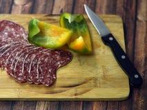 Salami und Paprika auf hölzerner Platte Stockbilder