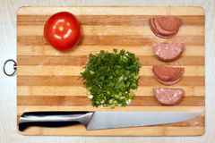 Salami and Vegetables. Salami, knife  and Vegetables on wooden plate Royalty Free Stock Photography