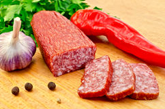 Salami with vegetables on the board Stock Photos