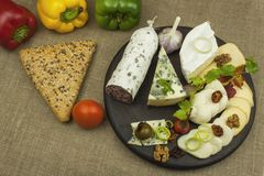 Salami with walnuts. Delicious specialty. Different kinds of cheese and vegetables. Stock Photo