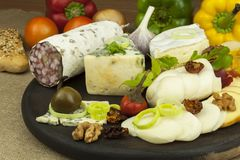 Salami with walnuts. Delicious specialty. Different kinds of cheese and vegetables. Royalty Free Stock Images