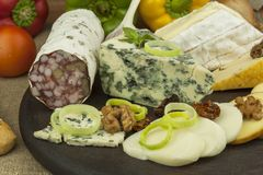 Salami with walnuts. Delicious specialty. Different kinds of cheese and vegetables. Stock Images