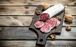 Salami with walnuts. On a wooden background stock image