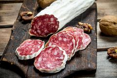 Salami with walnuts. On a wooden background stock images