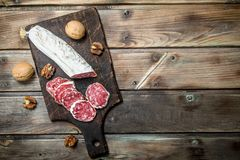 Salami with walnuts. On a wooden background royalty free stock photos
