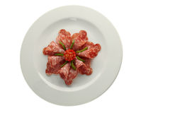 Salami on white plate. Salami and green peppers on white plate Stock Photo