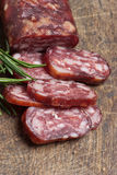 Salami on wooden background Stock Photography