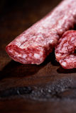 Salami on wooden background Royalty Free Stock Images
