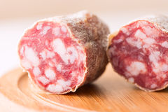 Salami on wooden board close up Royalty Free Stock Images