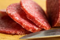 Salami on wooden cutting board with knife, macro photo with selective focus. Slices of sausage royalty free stock images