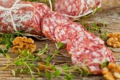 Salamikorvar som skivas med peppar, vitlök och rosmarin på skärbräda på trätabellen arkivfoton