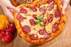 Salamipizza in den Händen Stockfoto