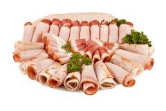 Salamischinkenfleisch und -mehr auf der Platte lokalisiert auf der Weißrückseite Lizenzfreie Stockfotografie