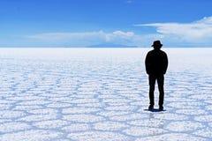 Salar de Uyuni Bolivia salt desert - lonely man silhouette. Salar de Uyuni Bolivia - panorama of the perfect white flat salt desert with blue cloudy sky. Lonely royalty free stock photos