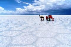 Salar de Uyuni Bolivia salt desert - lonely man. Salar de Uyuni Bolivia - panorama of the perfect white flat salt desert with blue cloudy sky. Lonely man sitting royalty free stock image
